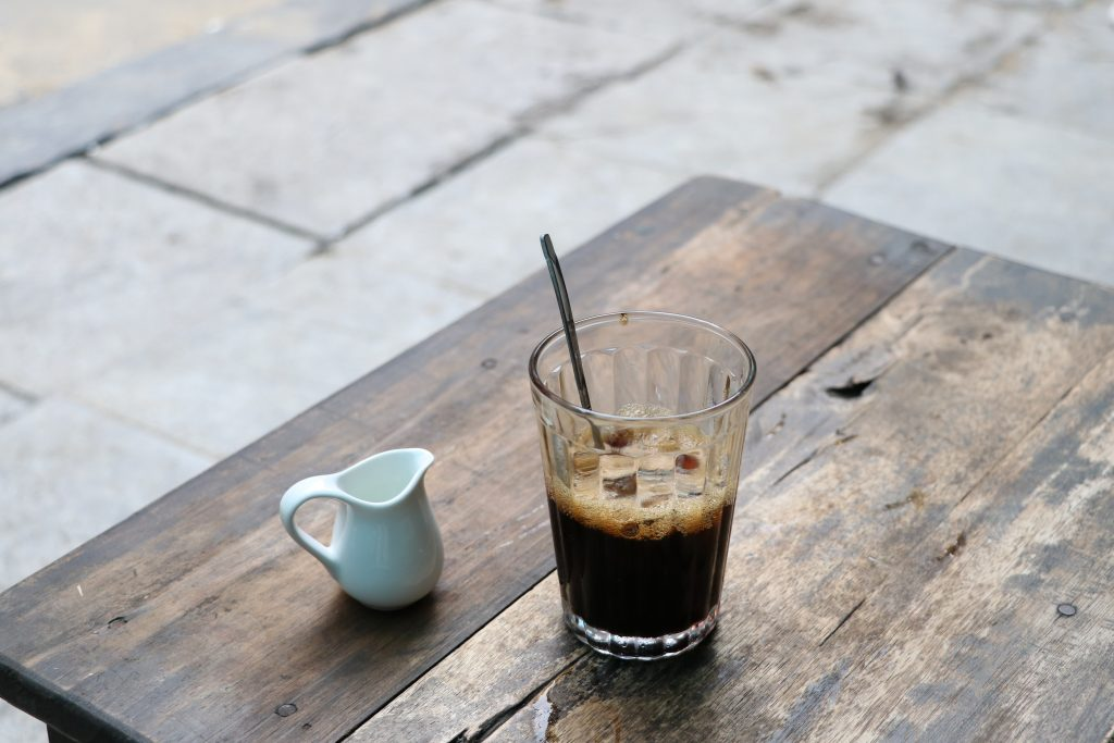 clear glass mug with black liquid on brown wooden table