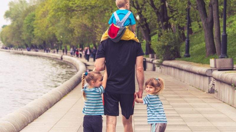 man in black t-shirt and brown shorts holding girl in blue and black jacket walking