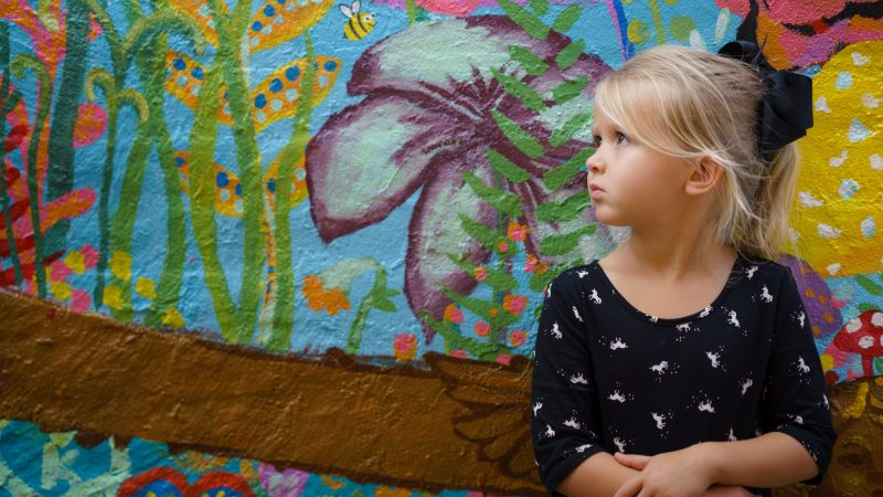 girl leaning on floral wall
