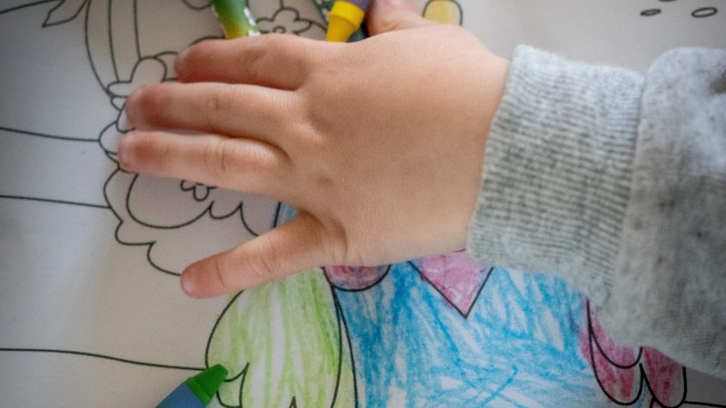 person holding green and white coloring pencils