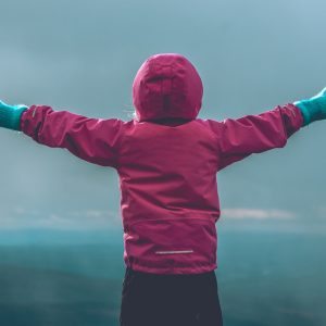 person wearing pink hooded jacket raising her hand in front of green mountain range during daytime