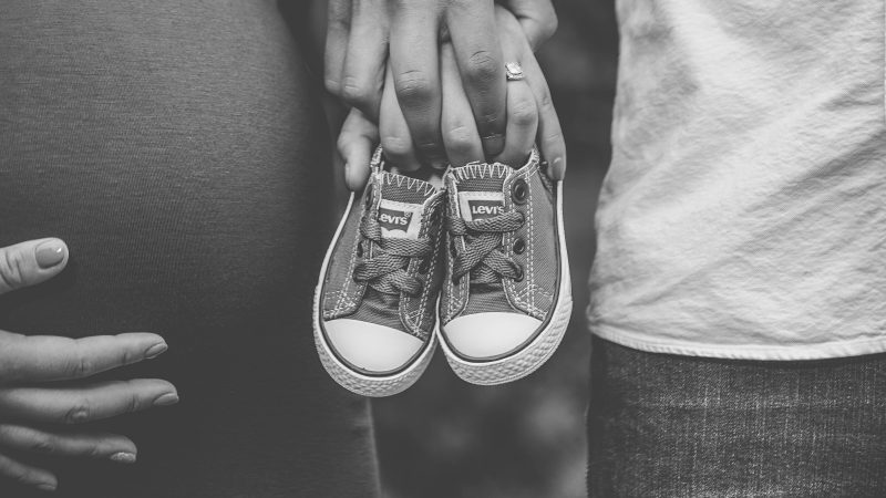 grayscale photo of man and woman holding baby's low-top shoes