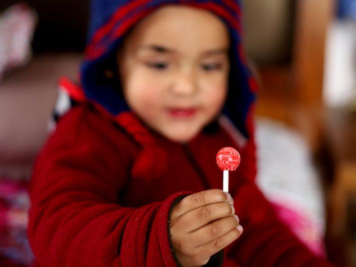 baby holding lollipop