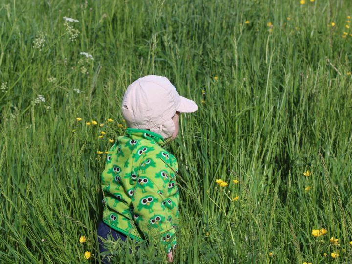child walking on green grass field during daytime
