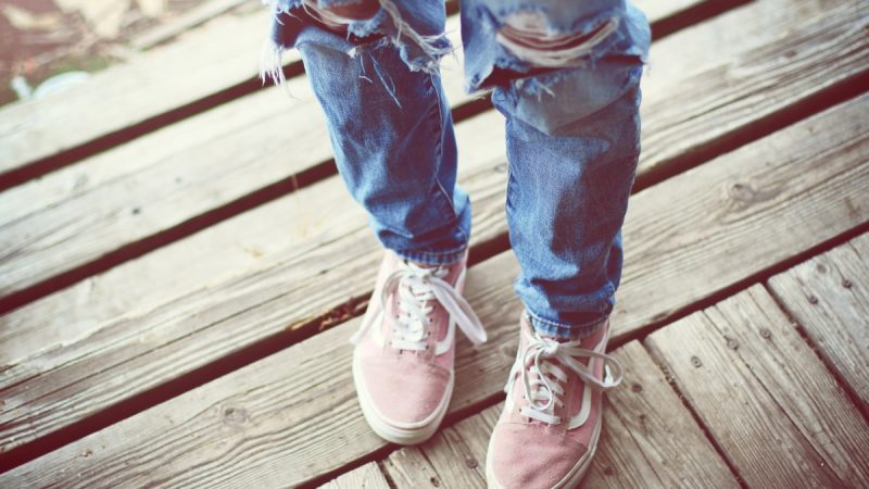person in blue denim jeans and brown and white sneakers