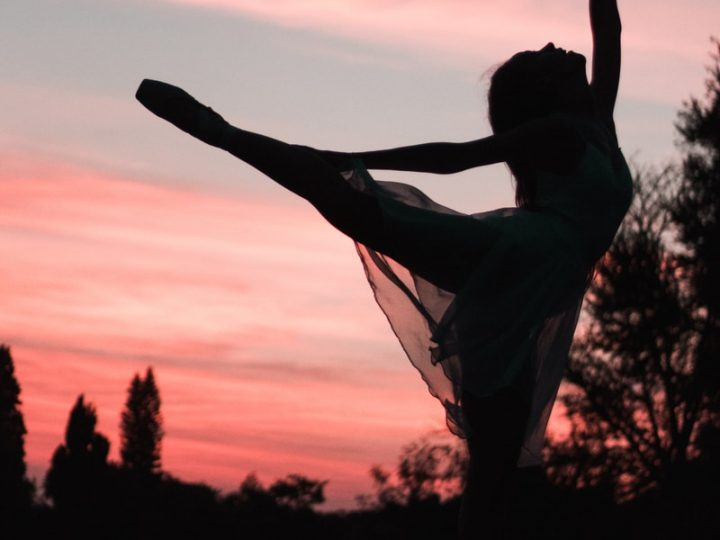 silhouette of woman standing on hammock during sunset