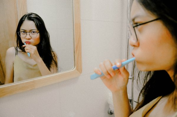 woman brushing teeth in front of mirror
