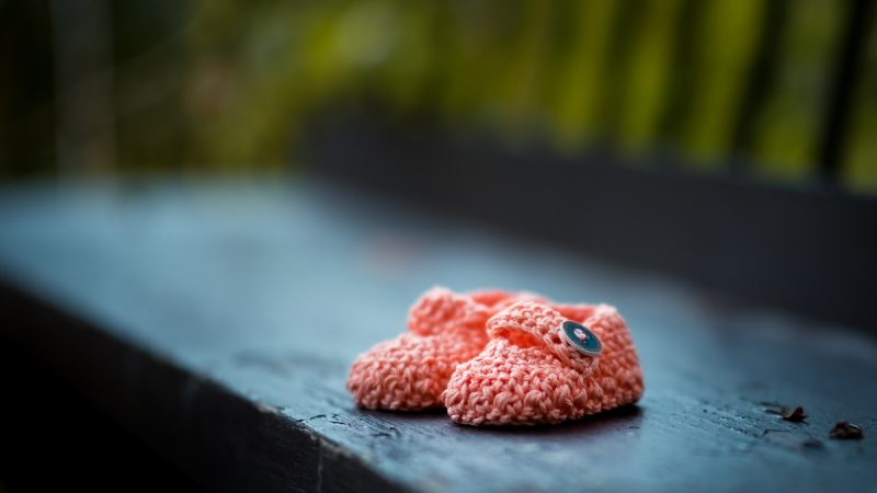 pair of baby's pink knit shoes on bench