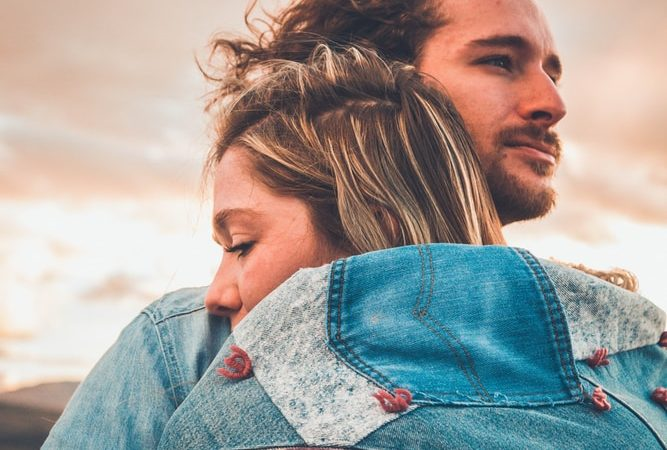 selective focus photography of couple hugging